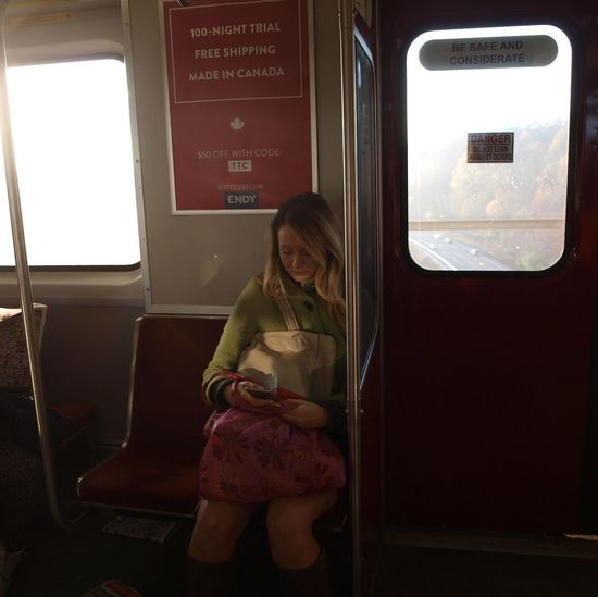 Absorbed In Phone Contemplative Moment On Subway Mode Of Transport One Person One Woman Only Passenger Riding Transit In Toronto Sitting Transportation Travel Travelling On Tr Window