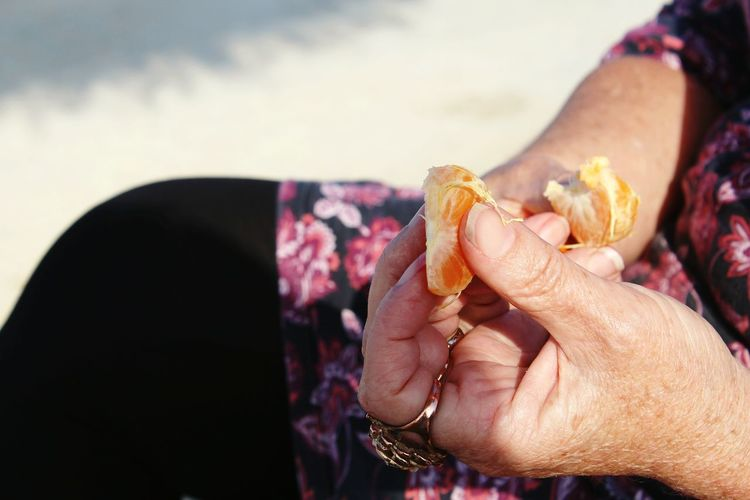 Close-Up Of Hands Holding Orange Slices