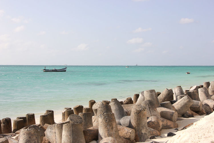 Scenic View Of Concrete Blocks On Beach Against Cloudy Sky
