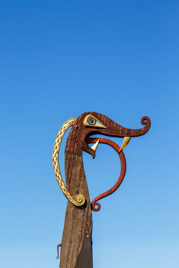 Low angle view of bird sculpture against clear blue sky