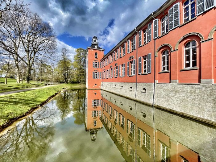 Canal by building against sky in city