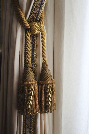 Close-up of tassels hanging by curtain