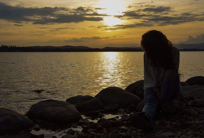 Sunset One Person Sitting Only Women Nature Water Women Beauty In Nature Sky Relaxation Lake One Woman Only Full Length Tranquility Real People Outdoors Beach Scenics Light And Shadow Skyline EyeEm Best Shots EyeEm Horizon Over Water Tranquility Beauty In Nature