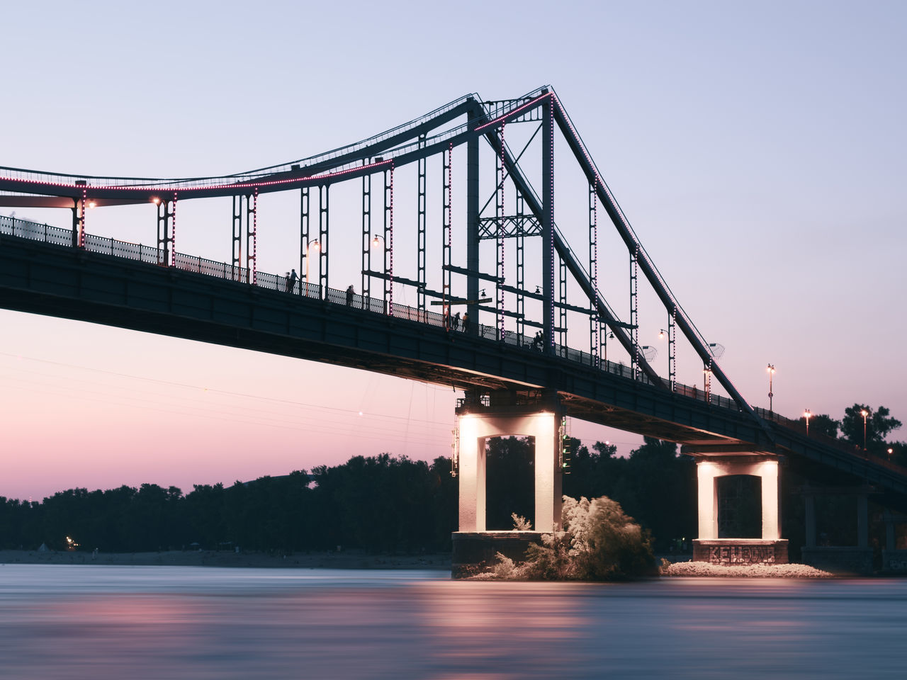 Low Angle View Of Bridge Over River Against Clear Sky At Dusk