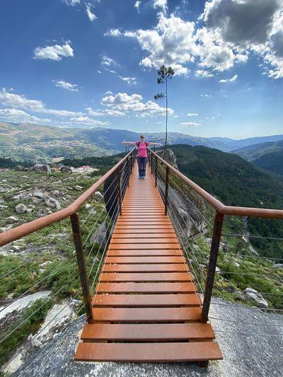 Rear view of footbridge on mountain against sky