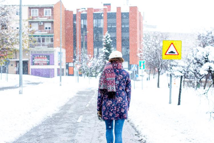 Rear view of man walking on road in winter