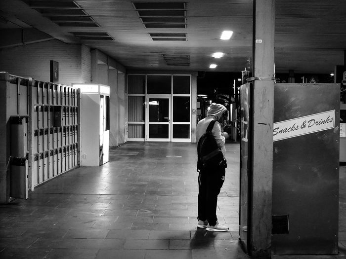 Man standing by snack vending machine at railroad station