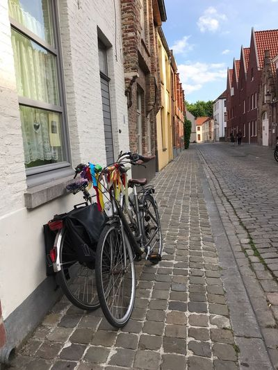 Bicycle parked on street amidst buildings in city