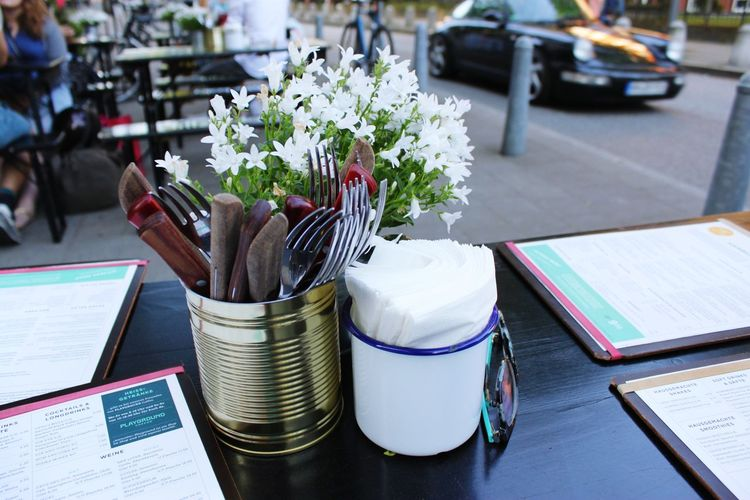 Close-up of cutlery in container by flowers at sidewalk cafe