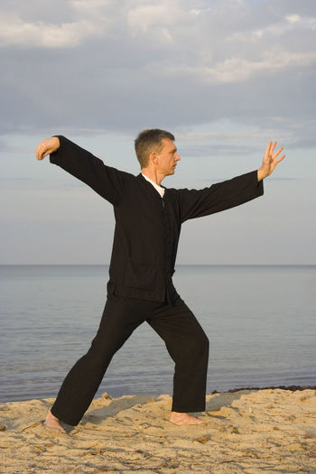 Full length of man practicing tai chi on shore at beach against sky