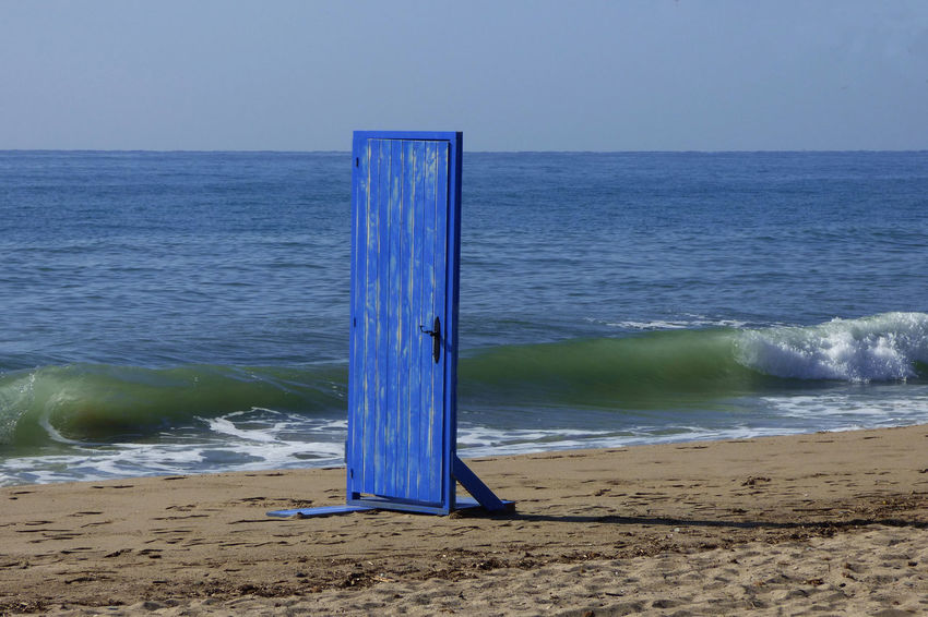Beach Beauty In Nature Blue Clear Sky Door Door On The Beach Horizon Horizon Over Water Idyllic Land Motion Nature No People Outdoors Sand Scenics - Nature Sea Sky Tranquil Scene Tranquility Water Wave Wooden Post