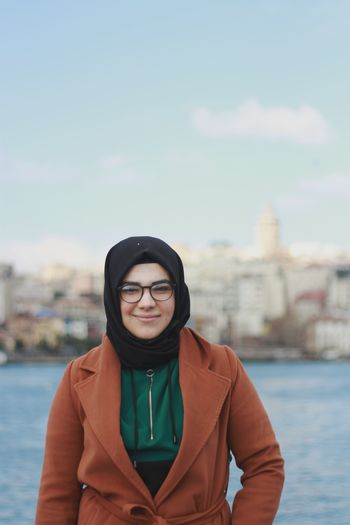 Portrait of smiling woman standing against cityscape