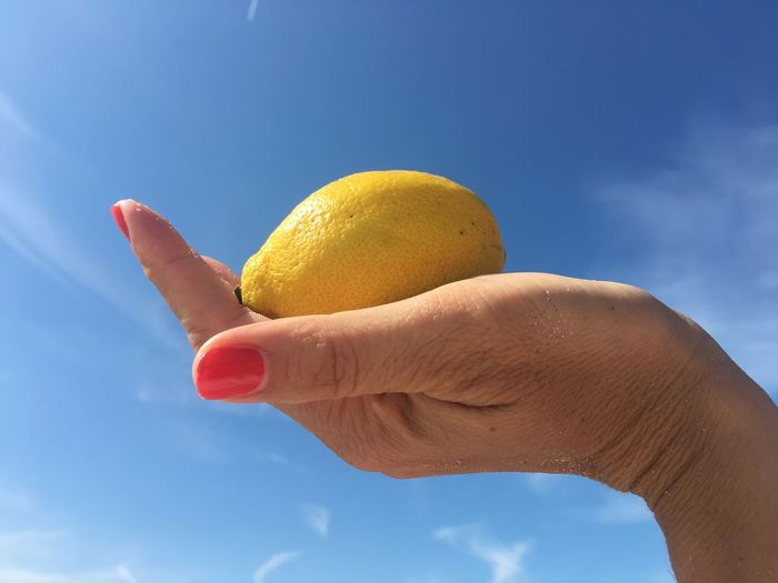 Low angle view of person holding ice cream against blue sky