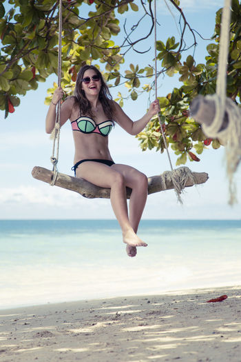 Full length portrait of young woman sitting on swing at beach against sky