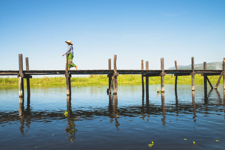 Everyday life on Inle Lake, Myanmar Asian  Inle Life Pier Travel Bridge Clear Sky Day Full Length Inle Lake Lake Lake View Mine Thaut Myanmar Myanmarphotos One Person Outdoors People Reflection Sky Standing Travel Destinations Travelphotography Water Wood - Material
