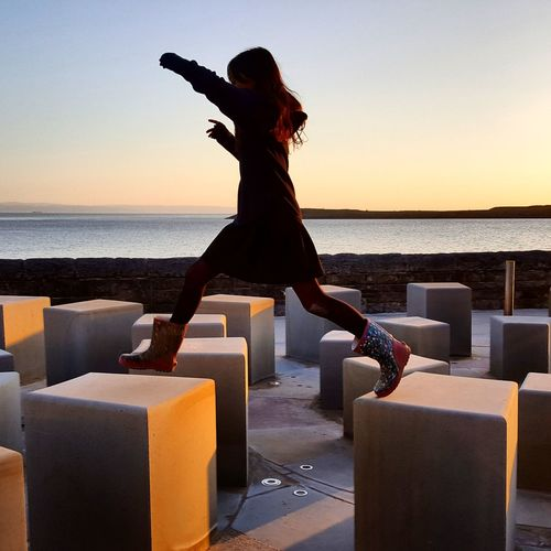 Full length of girl jumping on block shapes at promenade during sunset