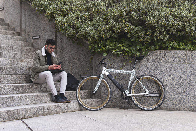 Man sitting on bicycle looking at city