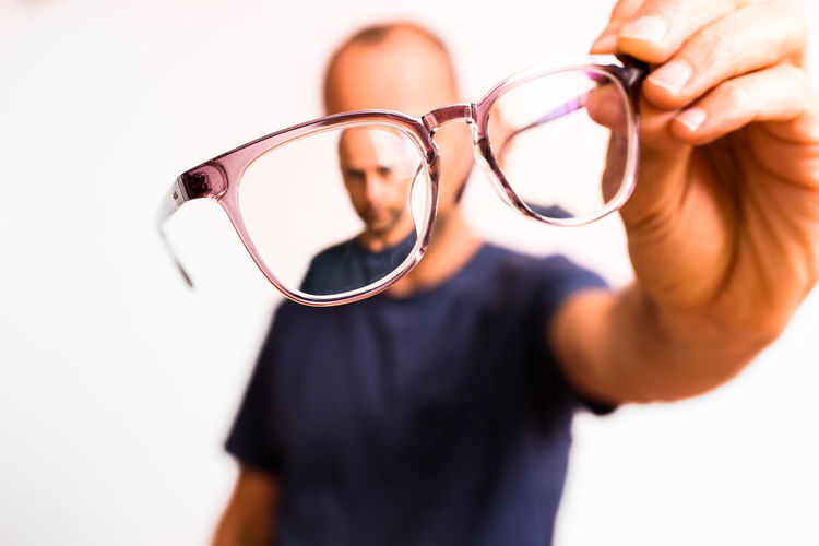 Midsection of man holding eyeglasses against white background