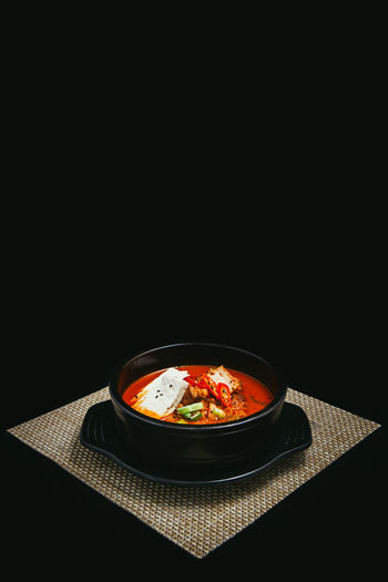 Close-up of soup in bowl against black background