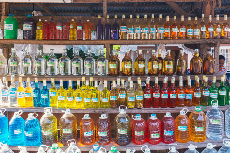 Multi colored bottles on display at market stall