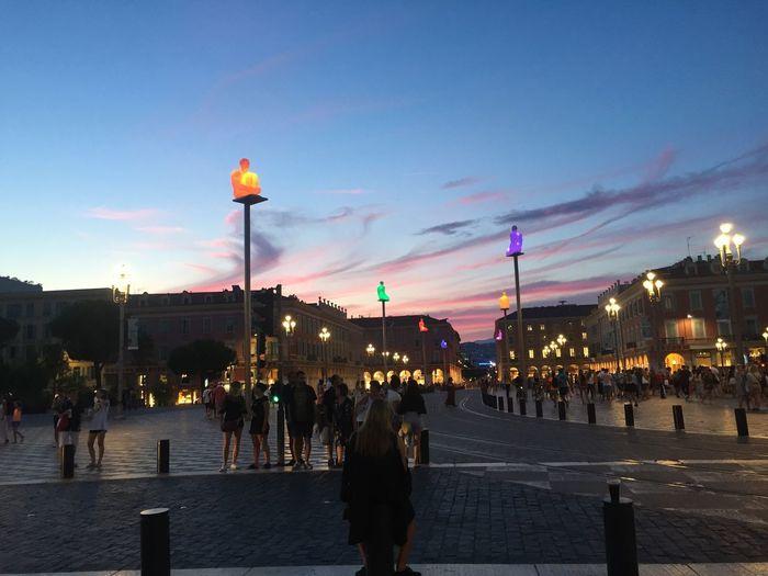 People walking on road in city against sky