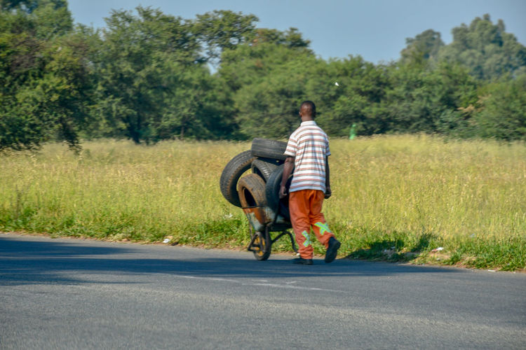 Transport old tyres with wheelbarrow. Roadside Side View Colors Grass Field Nature Travel Streetphotography Street Sky Clear Sky Wheel Blue Men People Motion Road Wheelbarrow Tyre Outdoors Lifestyles Landscape Adult One Person Day Full Length Tree Men Road Walking