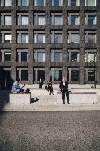 People walking on modern building in city