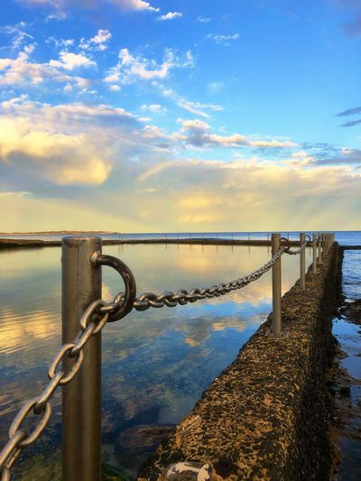 Metal railing by sea against sky during sunset