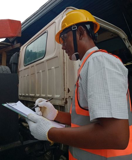 Side view of man working at bus