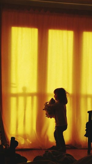 Side View Of Girl With Toy Standing On Floor At Home