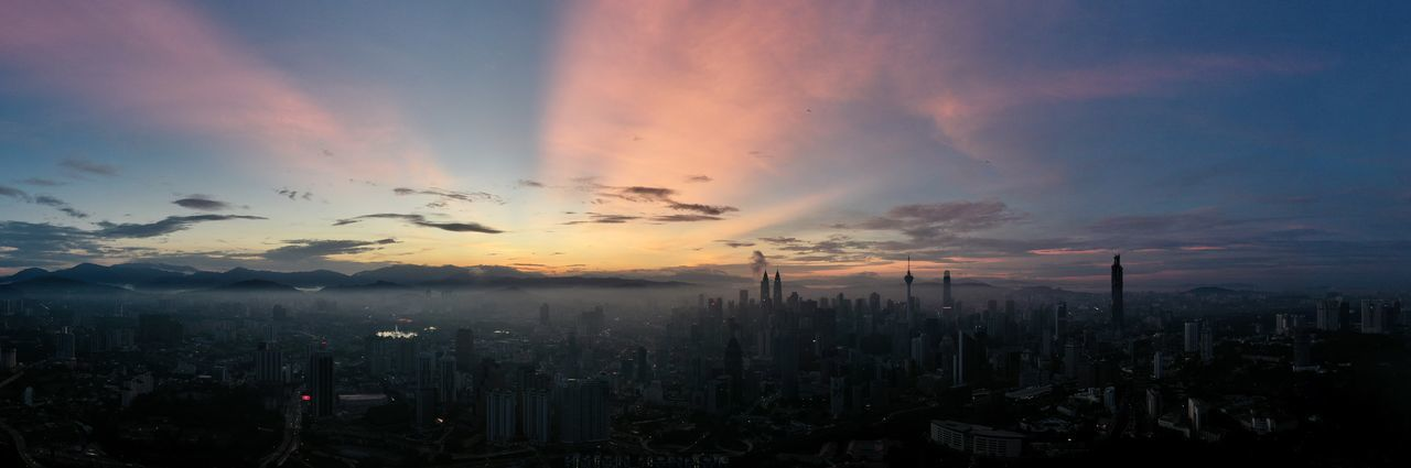 View of city against cloudy sky during sunset
