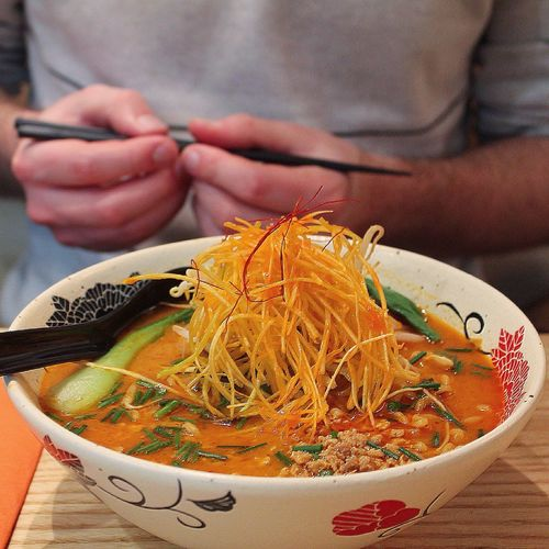 Midsection Of Man Holding Chopsticks While Having Ramen