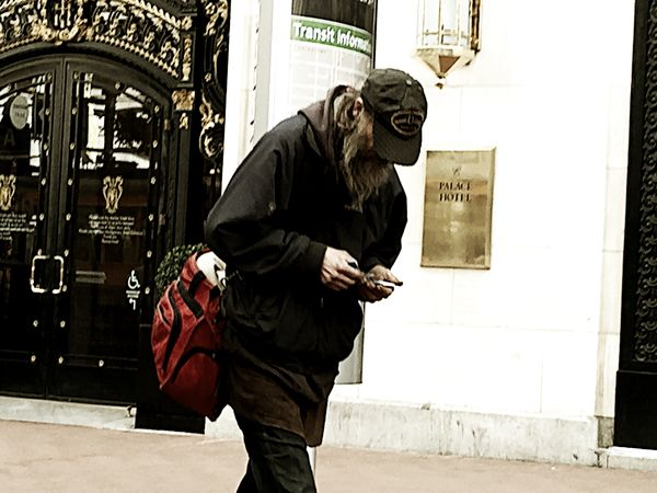 A homeless man walks past a luxury hotel. Backpack Building City Contrast Editorial  Homeless Man Juxtaposition Luxury Hotel Overcast Sidewalk Signs Urban Walking
