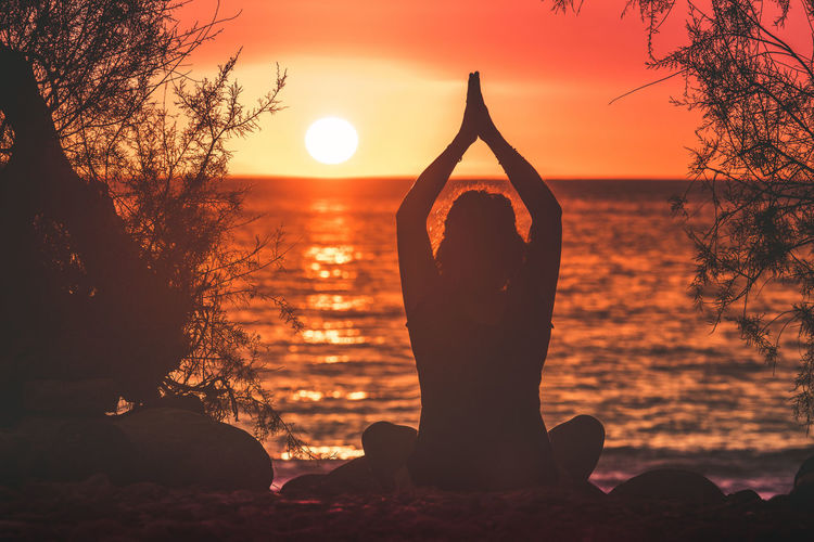 Silhouette image of a young woman making yoga lotus pose on a beautiful summer evening Back view of Girl with hands clasped sunset in background and and branches that frame Enjoyable romance feelings Sunset Sky Exercising Lifestyles Human Arm Yoga Beauty In Nature Leisure Activity Tree Tranquility Nature Wellbeing Sun Hand Outdoors Posture Helthy  Meditation Positive Concentration Lotus Energy Romance Harmony Exercise