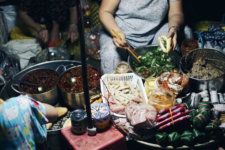 Midsection Of Woman Preparing Street Food At Night