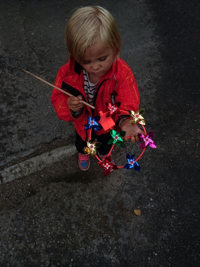 High Angle View Of Girl Holding Pinwheel Toy On Footpath