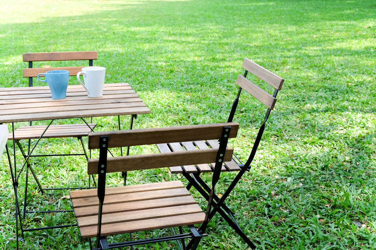 Empty chairs and table in park