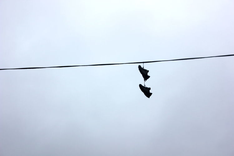 Low angle view of shoes tied to cable against sky