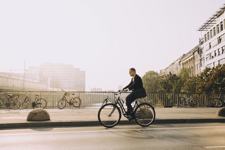 Man riding bicycle on city against sky