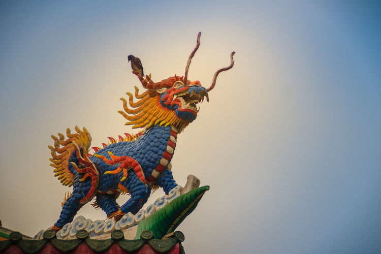 Chinese dragon-headed unicorn statue on the temple roof. Kylin or Kirin on roof in Chinese temple. Chinese Temple Ancient Architecture Chinese Temple Detail Kylin Roof Rooftop Statue Unicorn Unicorn Art Unıcorn Animal Animal Representation Arms Raised Art And Craft Blue Chinese Dragon Chinese Shrine Chinese Temple Chinese Temple Decoration Chinese Temples Clear Sky Copy Space Craft Creativity Day Dragon Dragon-headed Dragon-headed Unicorn Kirin Kyline Low Angle View Multi Colored Nature No People Outdoors Representation Roof Tile Rooftop View  Rooftops Sculpture Sky Statue Temple Roof Temple Roof Tile Unicorns