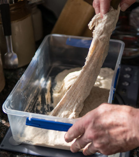 Cropped hands of woman kneading dough in container