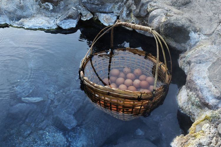 High angle view of wicker basket with brown eggs in hot spring