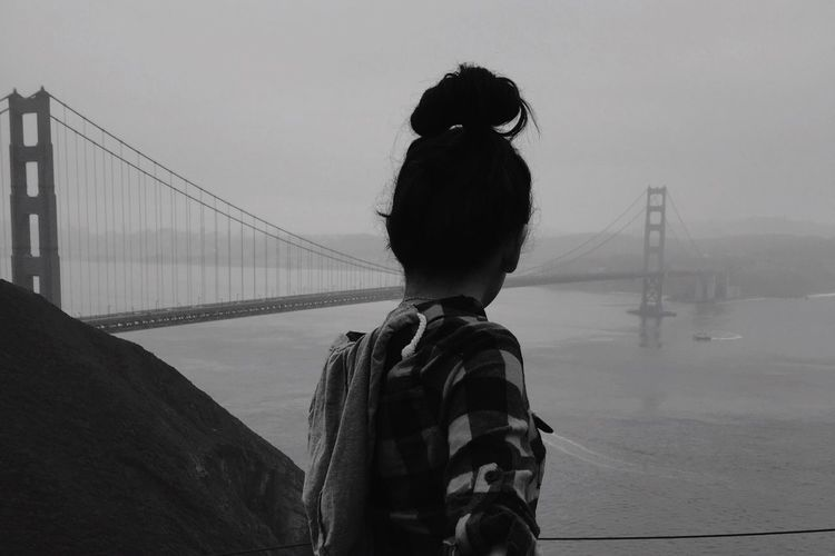 Rear view of young woman looking at golden gate bridge
