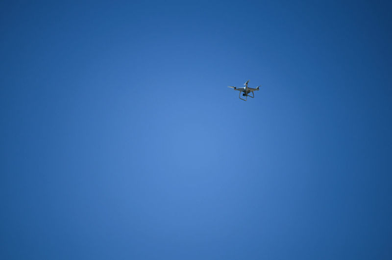 Low angle view of airplane against clear blue sky