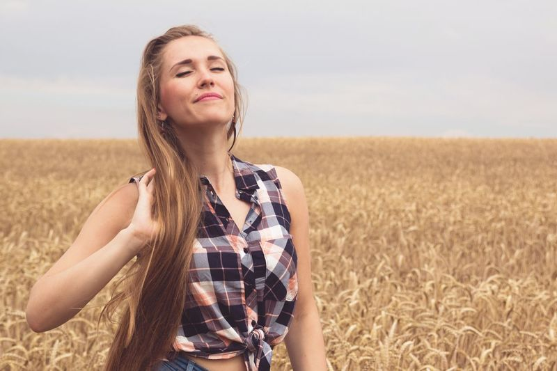 Young woman  standing in field against sky