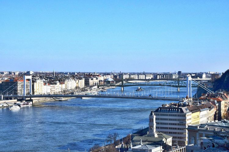 Bridges Over Danube River In City Against Blue Sky