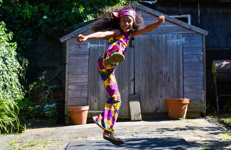 Full length of playful girl kicking while jumping at backyard