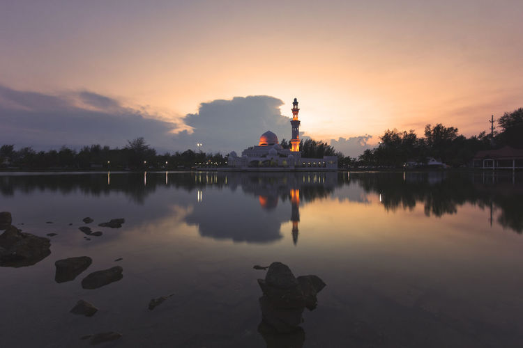Beautiful reflection of a mosque during sunset. Architecture Architecture, Mosque, Religion, Islam, Asia, East, Famous, Minaret, Muslim, Dome, Landmark, Islamic, Sunset, Travel, Sky, Arabic, Religious, Dusk, Building, Evening, Ramadan, Marble, Culture, Grand, Reflection, Nature, Sunrise, Belief, Stone, Pillars, Pat Beauty In Nature Building Exterior Built Structure Cloud - Sky Day Lake Nature No People Orange Color Outdoors Reflection Silhouette Sky Sunset Tree Water