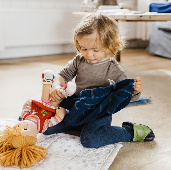 Toddler girl dressing doll in living room - Hindeloopen, Friesland, Netherlands Baby Blond Hair Care Caucasian Clothes Clothing Confidence  Curiosity Cute Doll Stuffed Toy Toy Domestic Life Domestic Room Getting Dressed Dressing Up Education Floor Sitting On Floor Girl Girls Hand Human Hand Holding At Home Ideas Individuality Jeans Joy Kids Learning Living Room Looking Down Germany Pampering Pants People Playing Playful Portrait Serious Toddler  Toddlerlife Concentration Trousers Child Childhood Real People Indoors  Sitting Lifestyles One Person Full Length Innocence Home Interior Casual Clothing Leisure Activity Females Women Focus On Foreground Flooring The Portraitist - 2019 EyeEm Awards