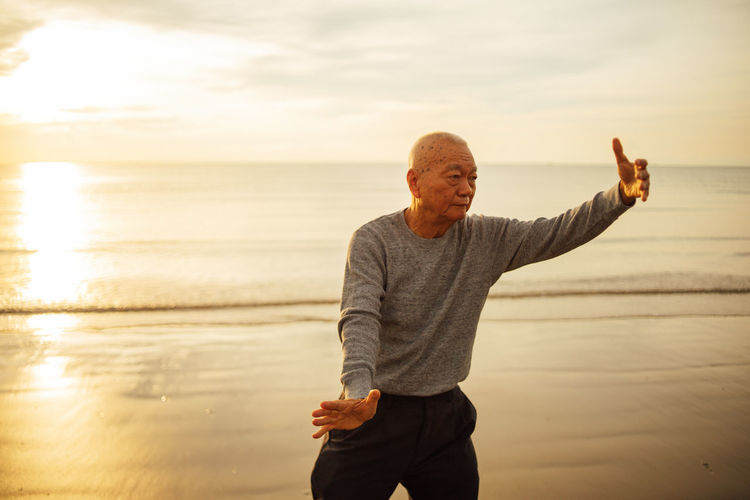 Senior man gesturing while standing on shore at beach against sky during sunset